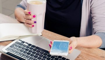 woman-holding-coffee-mug-and-text-messaging-with-laptop-on-wooden-table